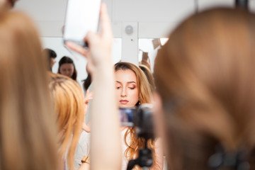 Woman with perfect makeup is photographed on smartphones from all around. Star and paparazzi
