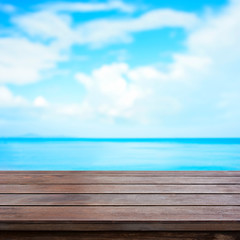 Old brown wood table top on blur sea and summer sky background