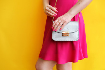 Wall Mural - Outdoor fashion girl in pink dress in hand little bag. Yellow wall .