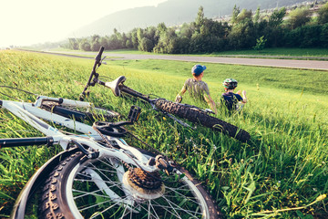 Father and son rest together in high green grass after bicycle walk