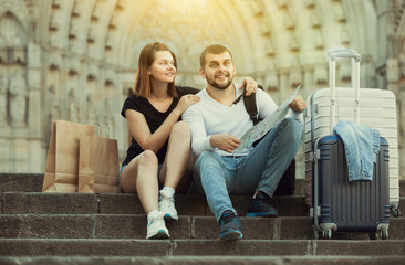 Smiling man and woman sitting at stairs with map