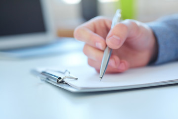 Male hand holding silver pen ready to make note in a clipboard. Businessman or employee at workplace writing business ideas, plans or tasks. Office life or education concept.