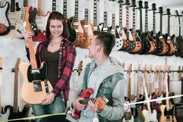 Teenagers choosing electric guitar