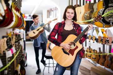 Teenage choosing best acoustic guitar
