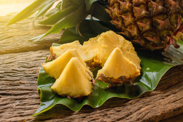 pineapple fruit cut on green leaf laying on the wood texture background