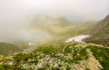 Steep slope on rocky hillside over balea lake in fog