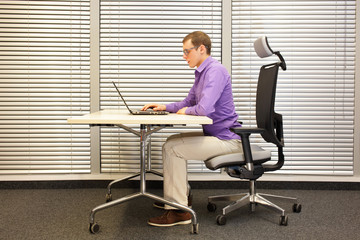 sitting position at workstation. man on chair working with laptop