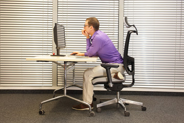 sitting position at workstation. man on chair working with pc