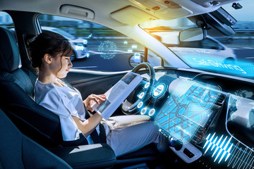 young woman using a smart phone in a autonomous car.  self driving vehicle. heads up display. automotive technology.