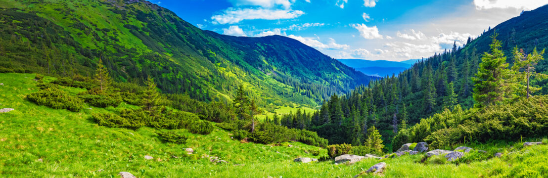 Majestic beautiful mountain valley on a summer day with clouds and blue sky