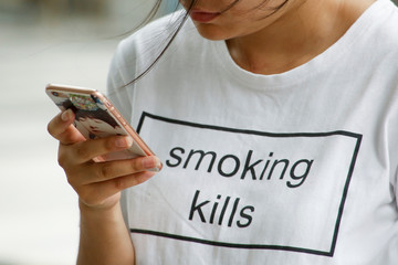 """A woman wearing a """"smoking kills"""" T-shirt uses a mobile phone in Beijing"""