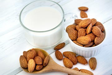 Close up healthy the almond milk in drinking glass with seed in white cup and wooden spoon on white wooden table plate with copy space