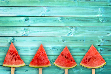 Four watermelon slice popsicles on blue wood background with copy space, fresh summer fruit concept