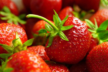 Background with berries of strawberry macro. The texture of a juicy fresh bright tasty strawberry close-up.