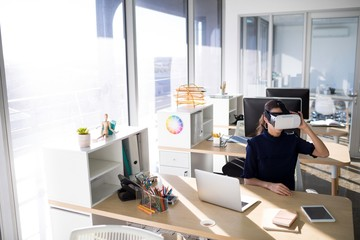 Female executive using virtual reality headset at her desk