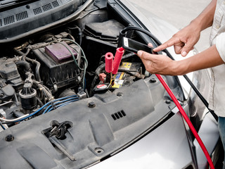 Man holding battery charging cables transferring power car
