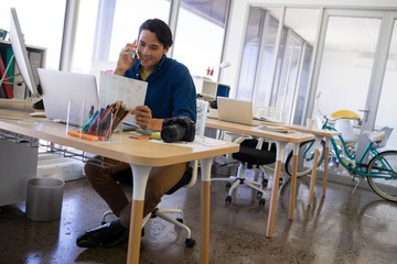 Male executive talking on mobile phone while working at his desk