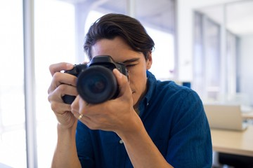Male executive clicking a picture on digital camera