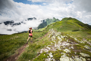young woman running alone on extreme adventure ultra trail with high mountain scenery and blue sky