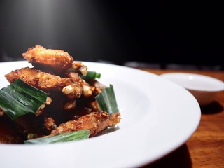 This dish is delicious but fat, The picture of deep fried chicken wings with pandan leaves on white plate, selective focus, dark background