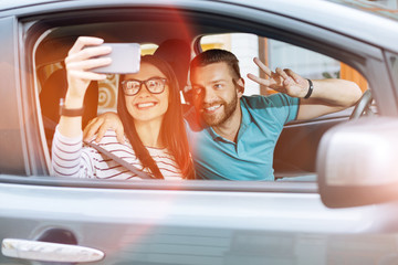 Beautiful young couple making selfies in a car