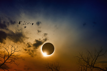 Total solar eclipse in dark red glowing sky