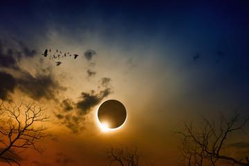 Total solar eclipse in dark red glowing sky