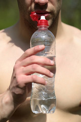 Thirsty man with beard and naked chest holds water bottle
