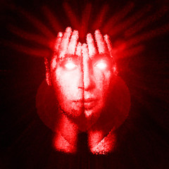Surreal portrait of a man covering his face and eyes with his hands. Face shines through hands. Double exposure