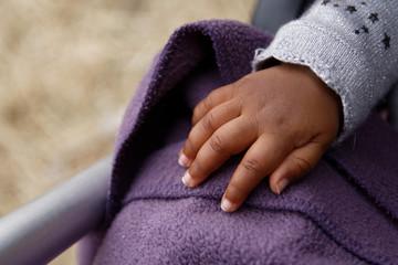 Main de bébé métis dans s& poussette