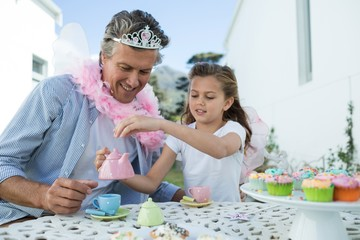 Smiling father and daughter in fairy costume having a tea party