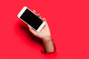 Hand with smartphone on red Wall mural