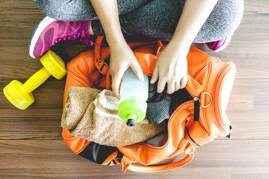 Woman with bag and fitness equipment