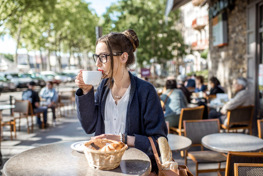 Young woman having a breakfast with coffee and croissant sitting outdoors at the french cafe in Lyon city