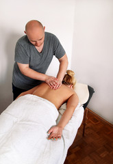 Back massage in beauty relax studio. Woman laying on massage table and having a massage back. Beautiful girl is enjoys, on front of her body while a massage therapist is massaging her back. Body care.