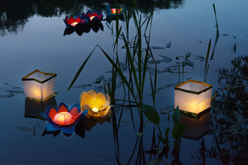 Water burning yellow lanterns on the lake amid tall grass