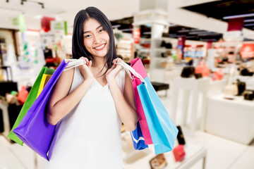 Happy woman holding shopping bags at shopping mall