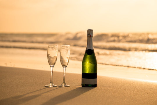 Two glasses and bottle of champagne on the golden sand of azure calm Caribbean seashore with waves in summer sunset time