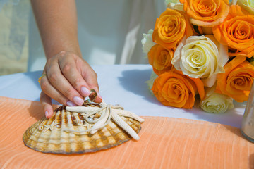 Woman holds a golden wedding ring near seashell and bouquet of orange roses at the seashore in summer sunny day