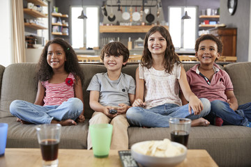 Group Of Children Sitting On Sofa Watching Television Together