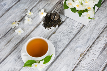 Jasmine dry green tea leaves with fresh jasmine flowers and white cup of green tea on wooden background. Top view.