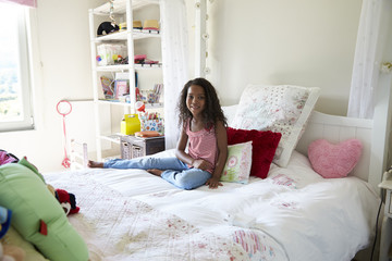 Portrait Of Young Girl Sitting On Bed In Bedroom