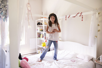 Portrait Of Girl Standing On Bed Listening To Music On Phone