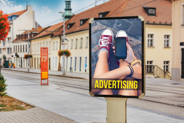 Billboards with advertising of a teenage girl with cellphone. At city street