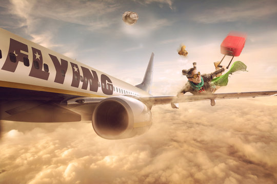 Woman flying in the wing of a moving plane, over clouds with luggage, lowcost holiday