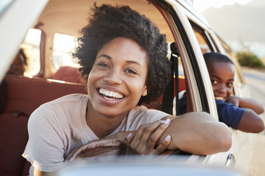 Portrait Of Mother And Children Relaxing In Car During Road Trip