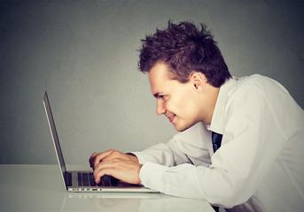 Happy man working on laptop computer
