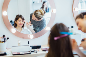 Backstage scene: Professional Make-up artist doing make up for young charming brunette woman in beauty modern salon.