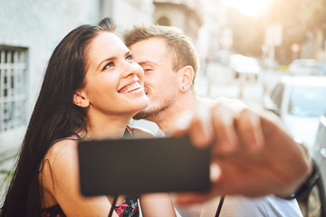 Young couple sitting at cafe and taking selfie