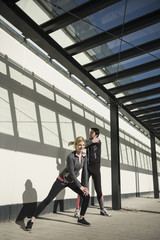 Man and woman in sportswear doing stretching on city footpath